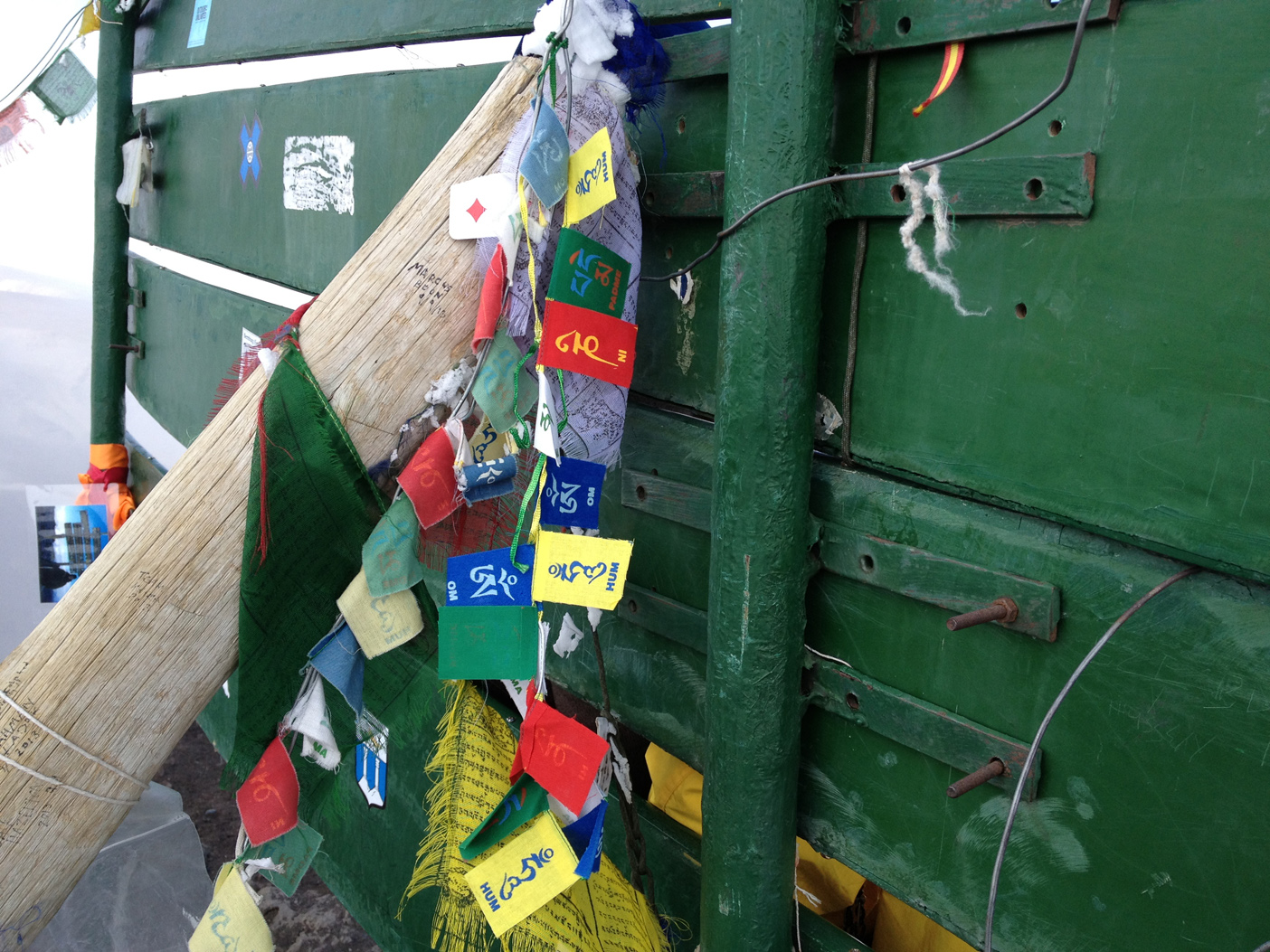 Prayer flags from Danny tied to the summit sign on Mt. Kilimanjaro
