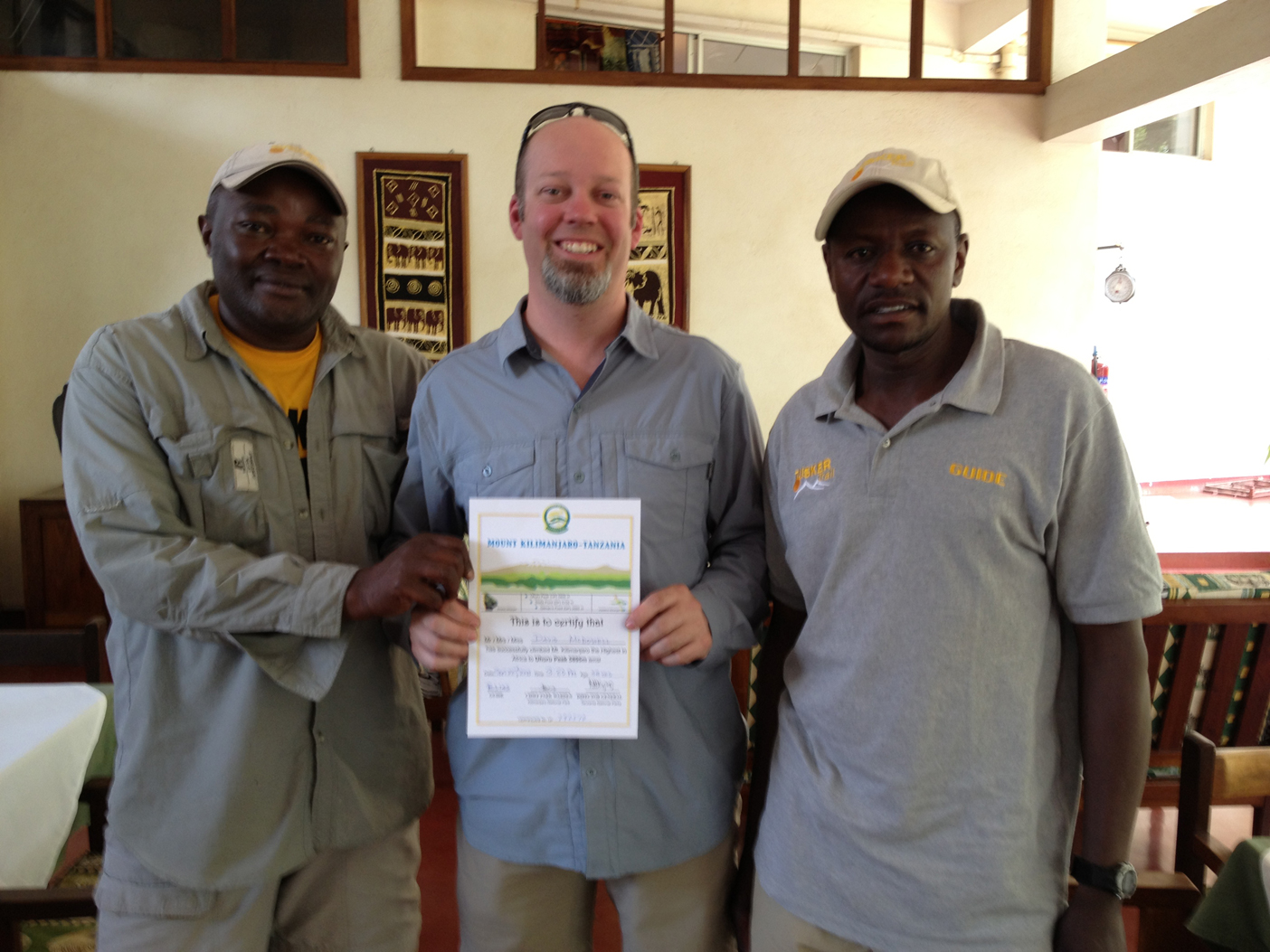Receiving my official Mt. Kilimanjaro summit certificate. (L to R) Elias (lead guide) , David McDowell, Gaudence (guide)