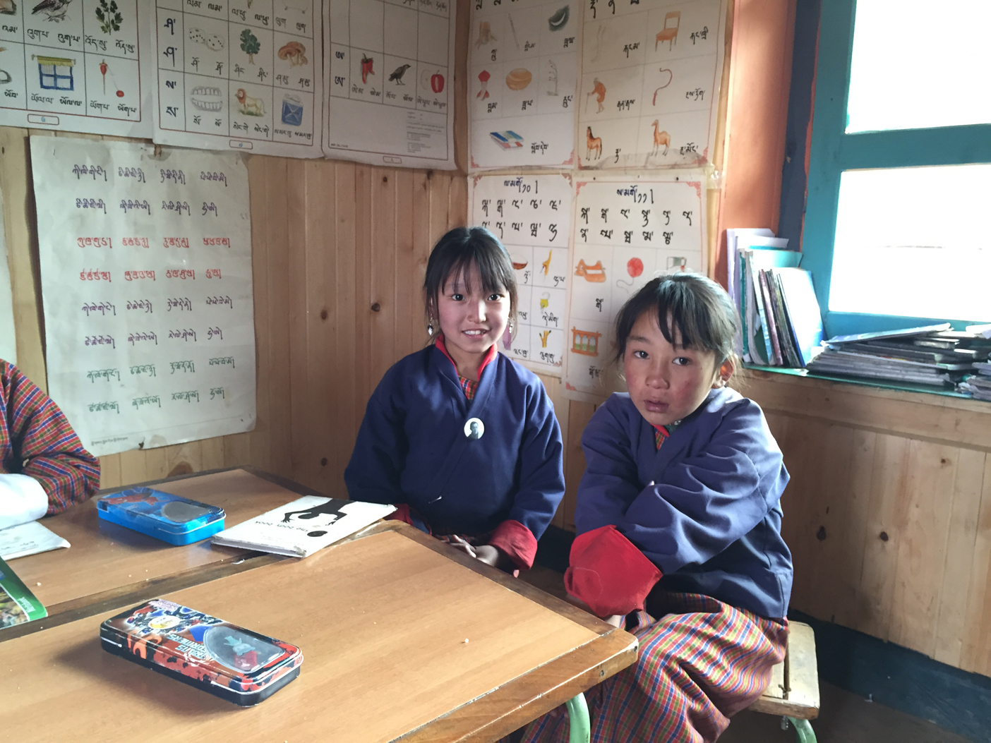 Two girls in the middle aged classroom, Bhutanese on the wall behind them, English on the opposite wall